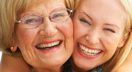 Tochter und Mutter umarmen sich und lächeln