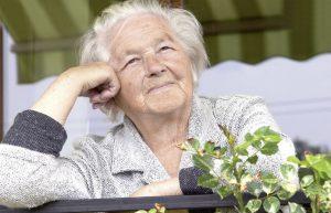 Ältere Dame sitzt auf ihrem Balkon, lächelt und schaut zufrieden in die Ferne.