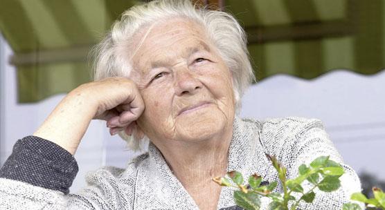 Ältere Frau sitzt auf dem Balkon, hat den Kopf auf die Hand gestützt und schaut zufrieden in die Ferne