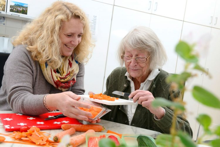 Pflegerin schneidet mit demenzkranker Frau Möhren für das Essen