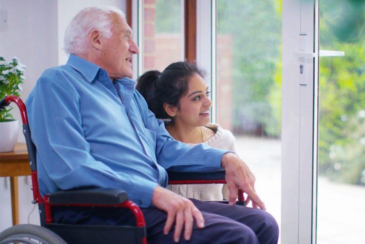 Demenziell veränderter Mann im Rollstuhl schaut zusammen mit seiner Pflegerin aus dem Fenster