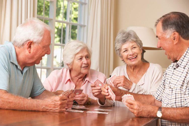 Gruppe von zwei alten Frauen und Männern spielen Karten und lachen