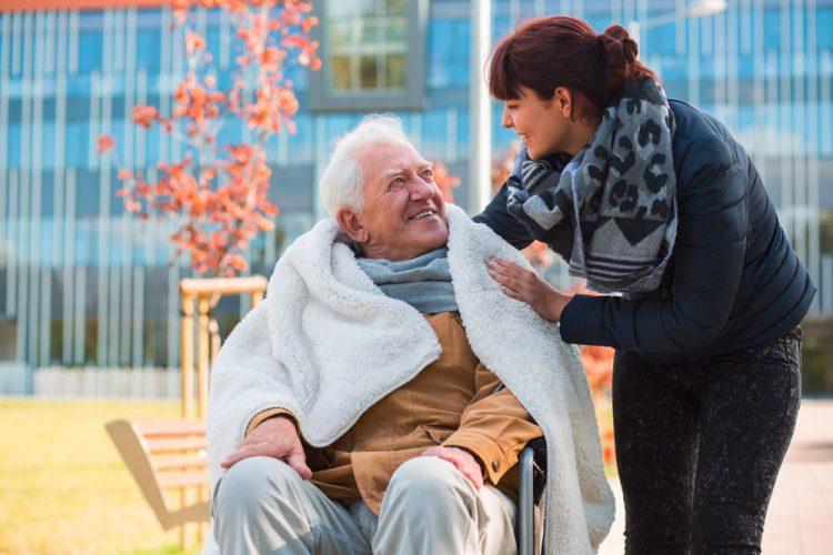 Alter Mann im Rollstuhl bekommt von junger Pflegerin eine weiße Decke