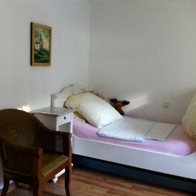 Bett mit Nachttisch und Korbstuhl in der Demenzwohngruppe und Demenzwohngemeinschaft Winterberg Bahnhofstr