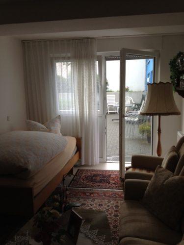 Einzelzimmer mit Bett und Zugang zur Terasse in der Demenzwohngruppe und Demenzwohngemeinschaft Geslenkirchen Dillbrinkstr