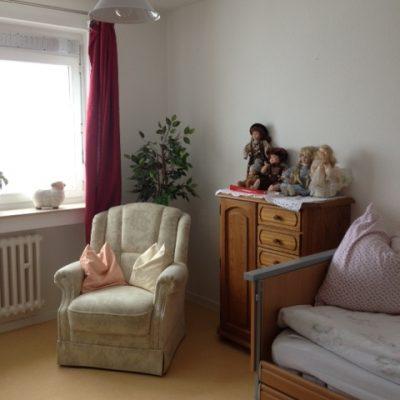 Zimmer mit Sessel und Bett in der Demenzwohngruppen und Demenzwohngemeinschaften Wuppertal Sternenberg